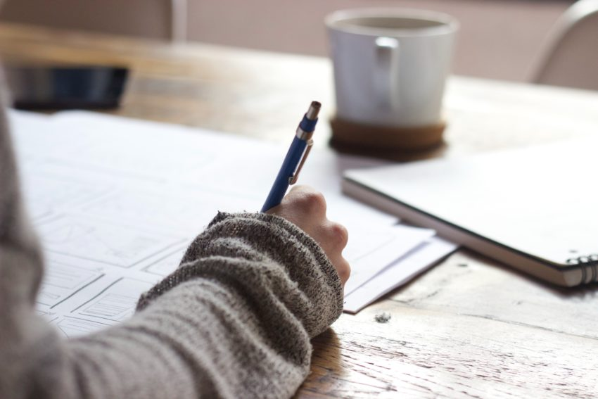 Photo of a person holding a pen.